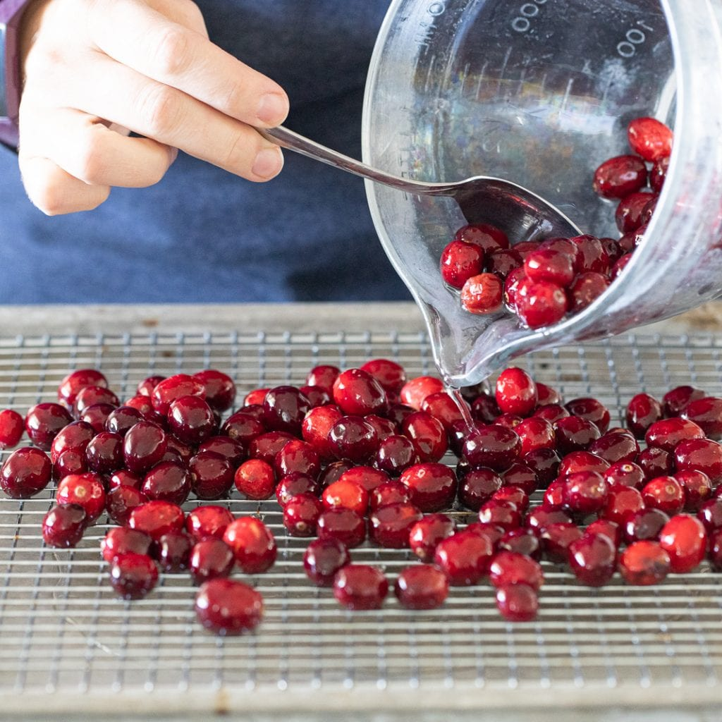 woman pouring cranberries for sugared cranberries onto cooling rack