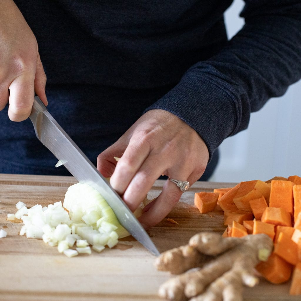 woman cutting onions on a wood cutting board with chef's knife