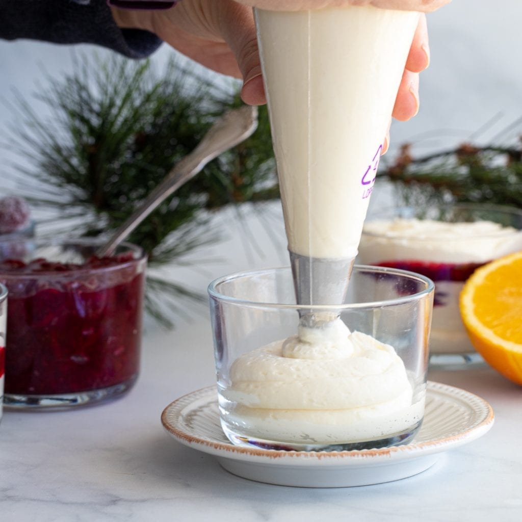 woman piping in white chocolate mousse to a clear dessert dish
