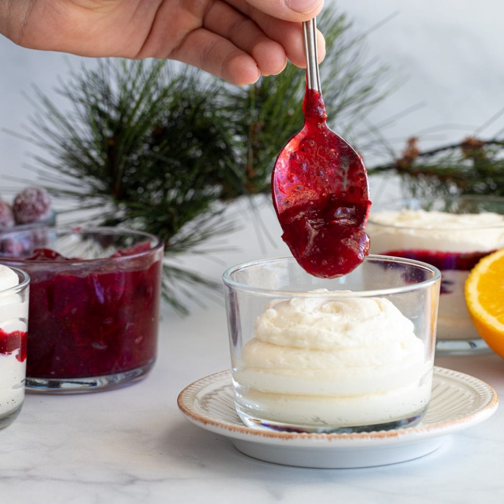 woman spooning cranberry sauce on top of white chocolate cream cheese mousse