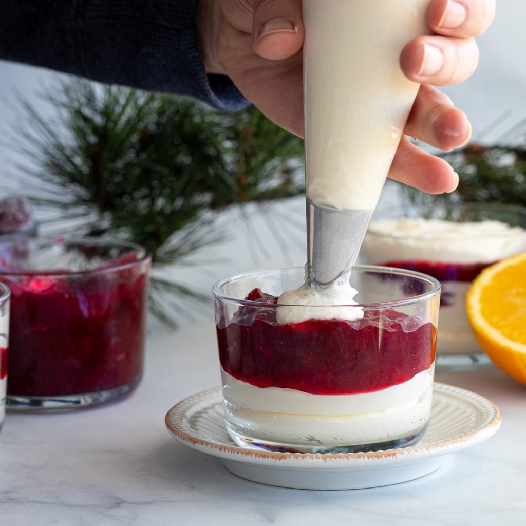 woman piping white chocolate cream cheese mousse on top of cranberry dessert