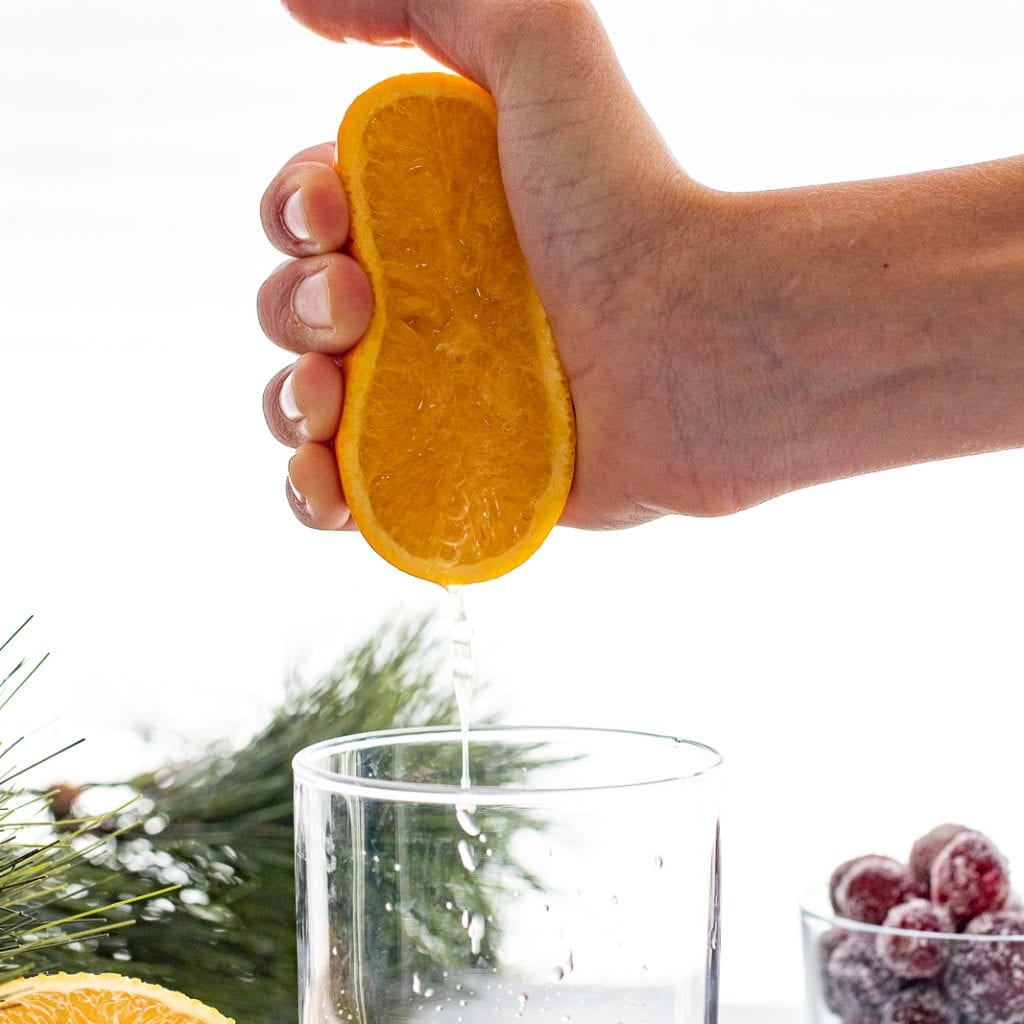 woman pouring fresh squeezed orange juice into glass cup
