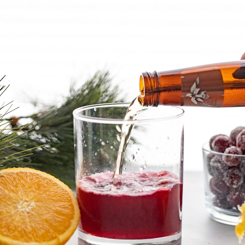 woman pouring vanilla soda into cranberry mocktail