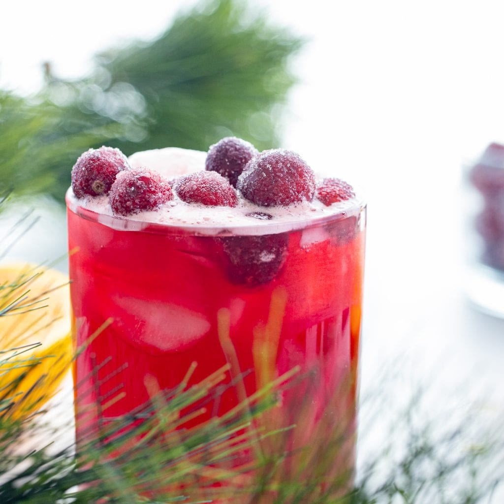 Cranberry Orange and Vanilla Mocktail in clear glass cup with  greenery in front with candied cranberries on top