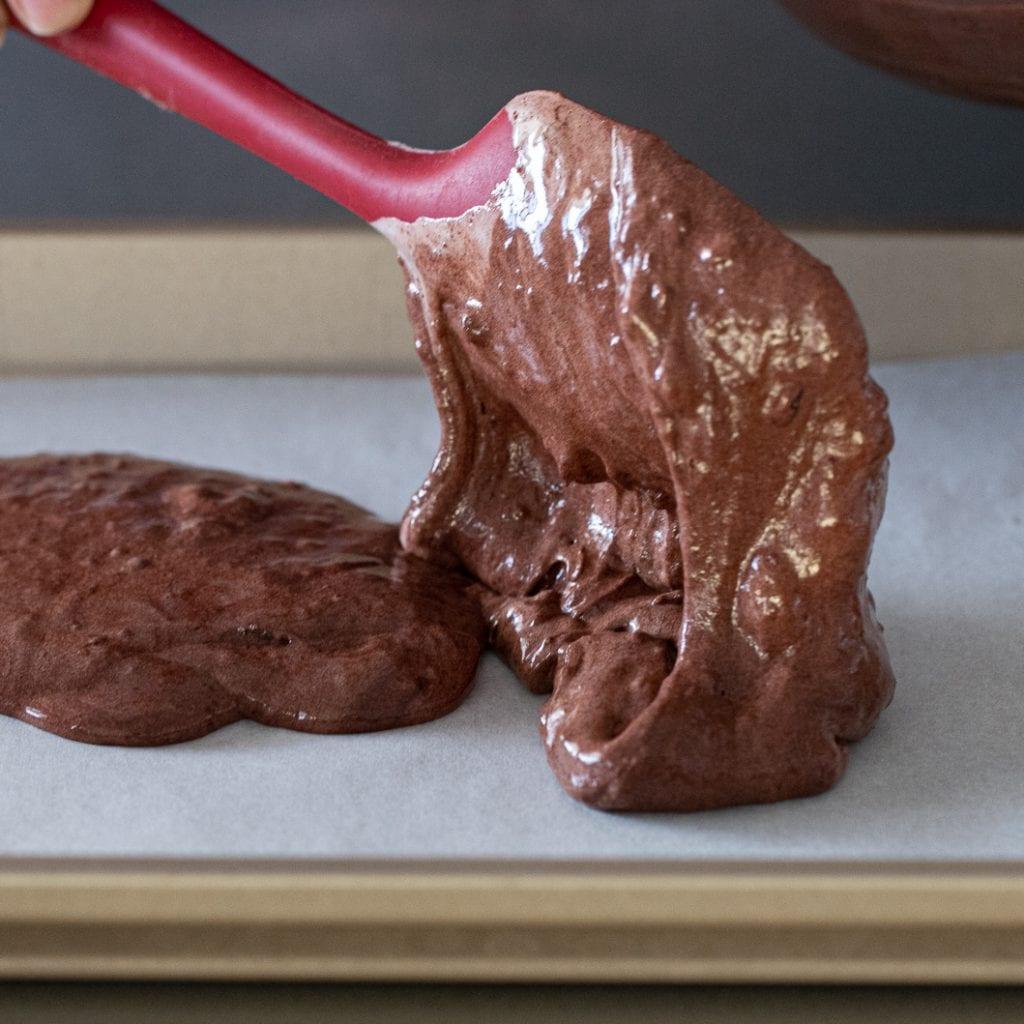 woman pouring chocolate cake batter onto jellyroll pan