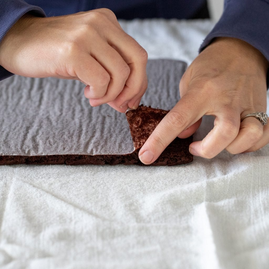 woman peeling parchment from back of baked jellyroll chocolate bake