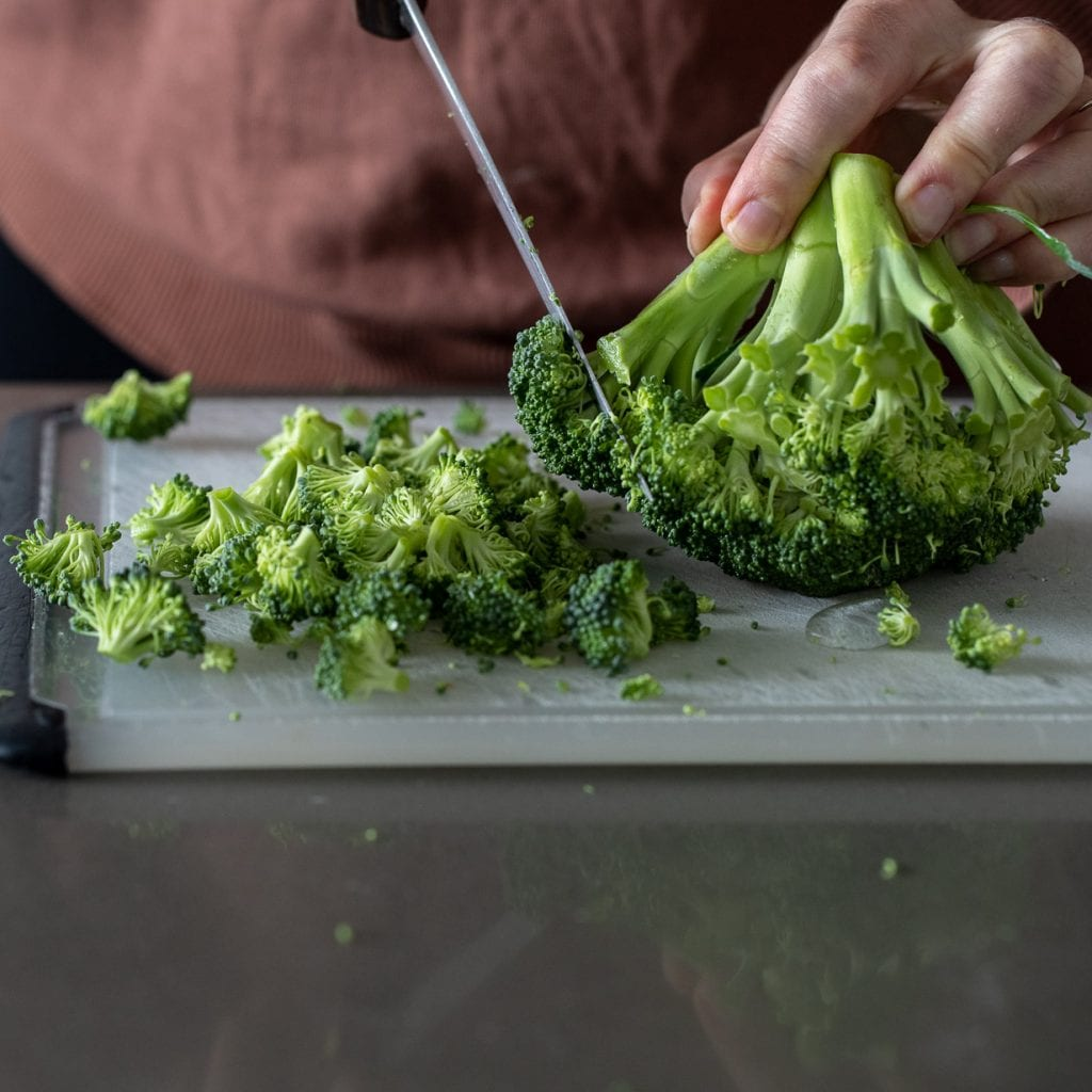 woman cutting broccoli off crown on a plastic cutting board for fritters.