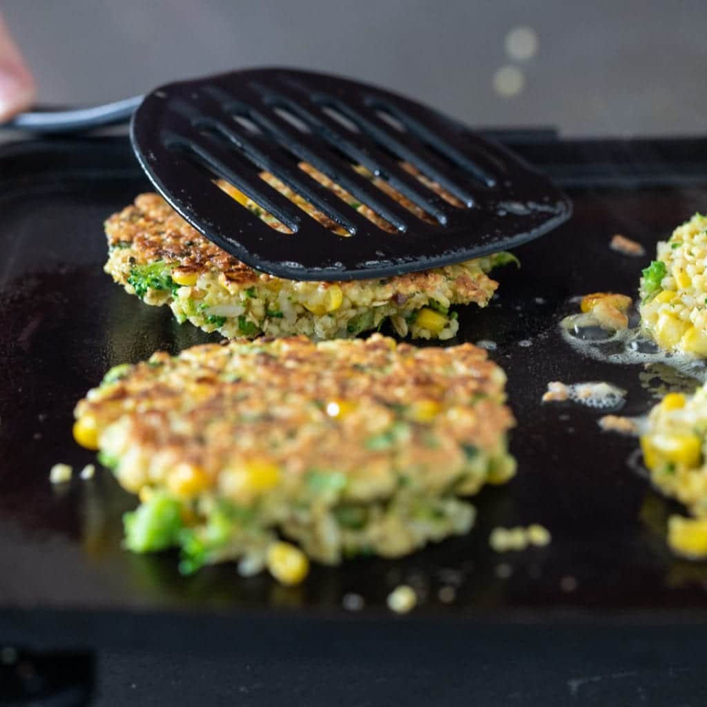 vegetable fritters cooking on a griddle