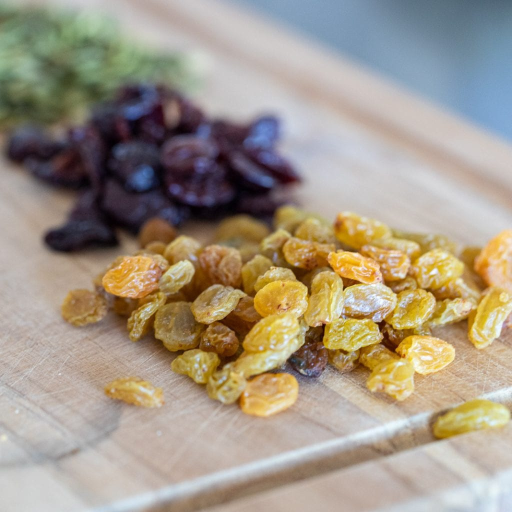 golden raisins on a cutting board