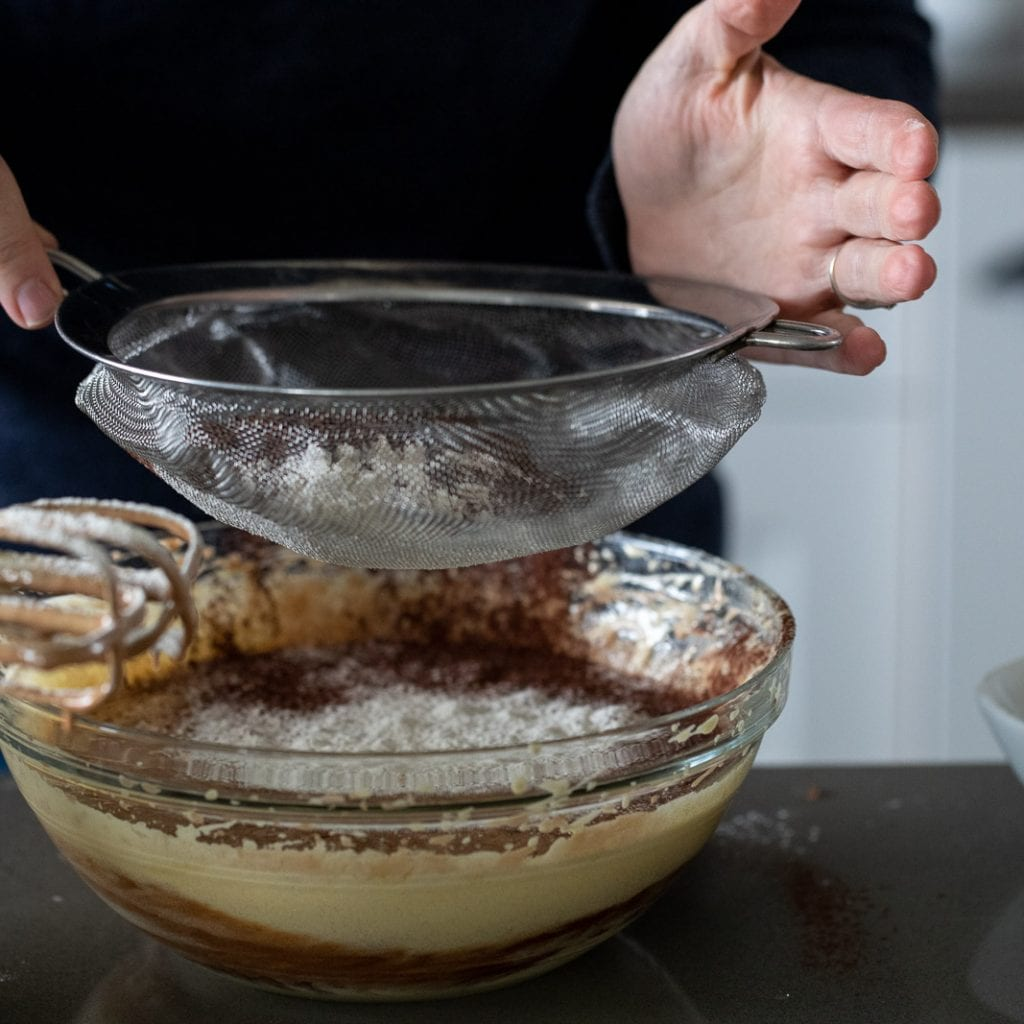woman sifting flour into brownie mixture
