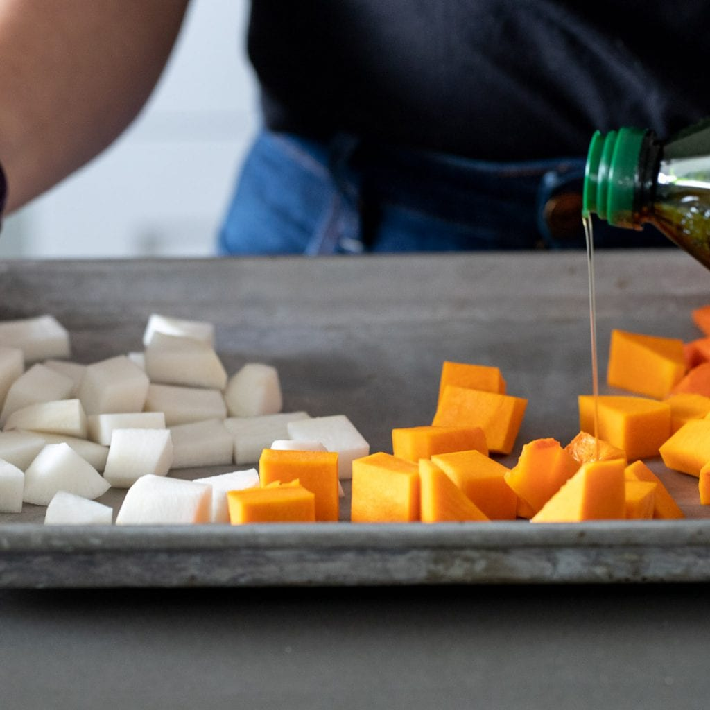 woman drizzling olive oil on a vegetables for roasting on a baking sheet