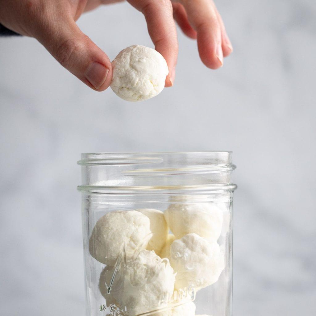 woman adding goat cheese to mason jar