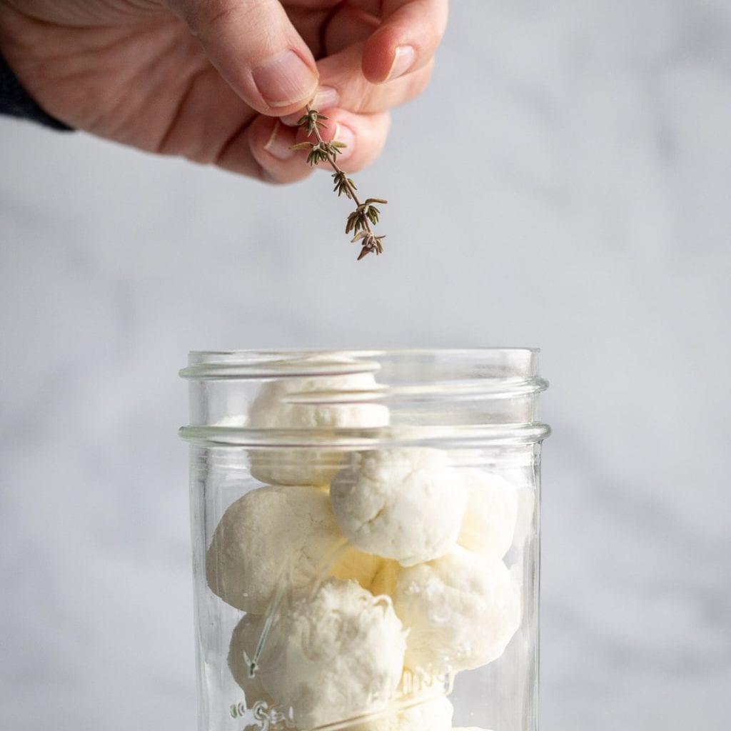 woman adding fresh thyme to goat cheese in a mason jar