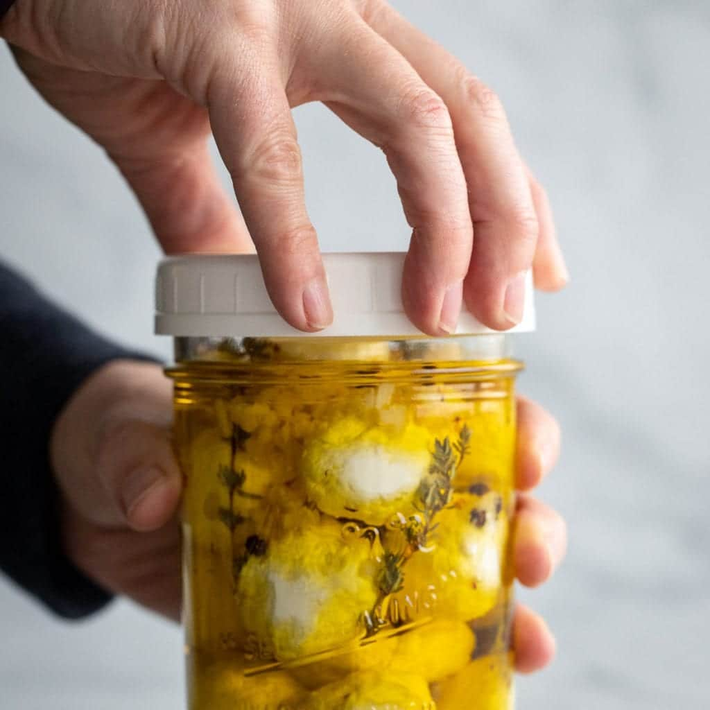 woman screwing the lid on a mason jar