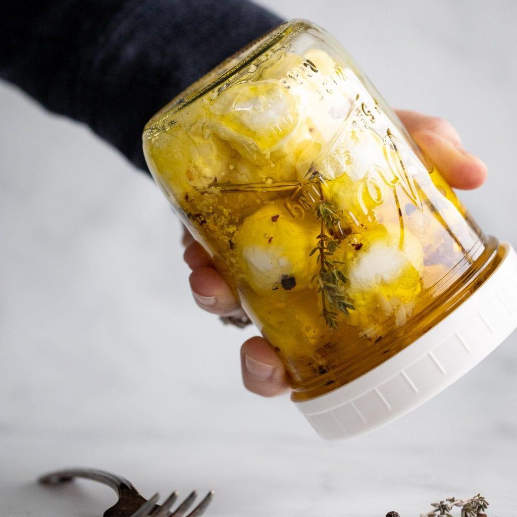 woman shaking marinated goat cheese in a mason jar