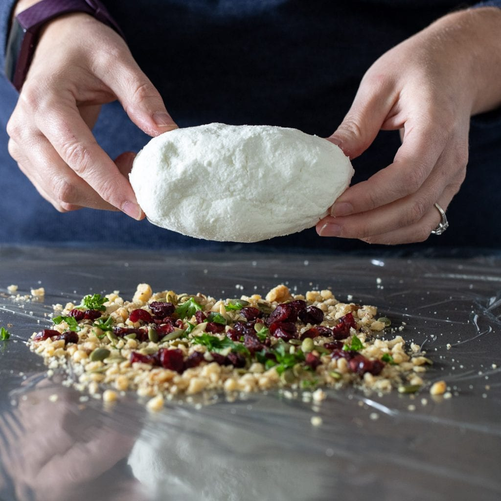 woman rolling goat cheese in dried fruit and nuts