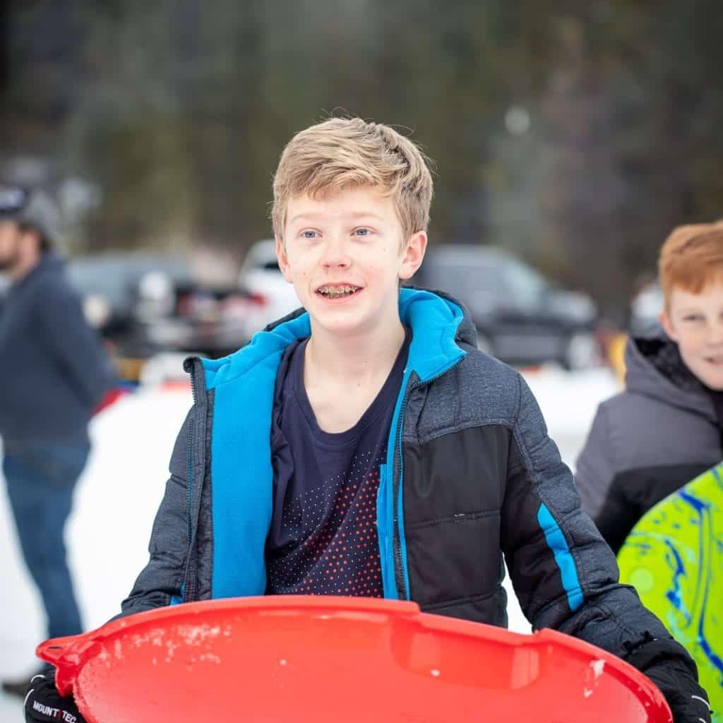 teenage boy holding saucer sled