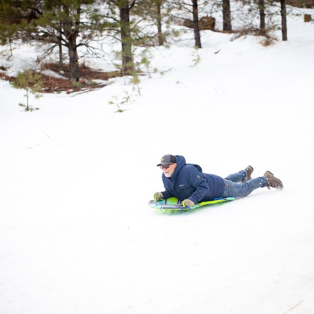 man sledding down sledding hill on a foam sled in an Eddie Bauer winter coat