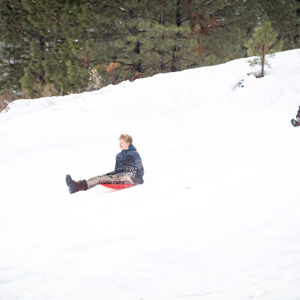 boy sledding down hill in saucer sled