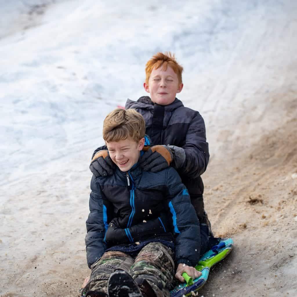 2 boys sledding down sledding hill