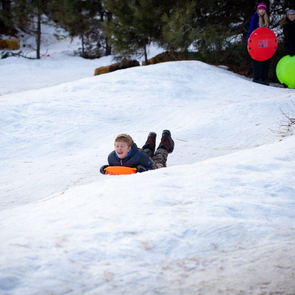teenage boy sledding down hill in toboggan.