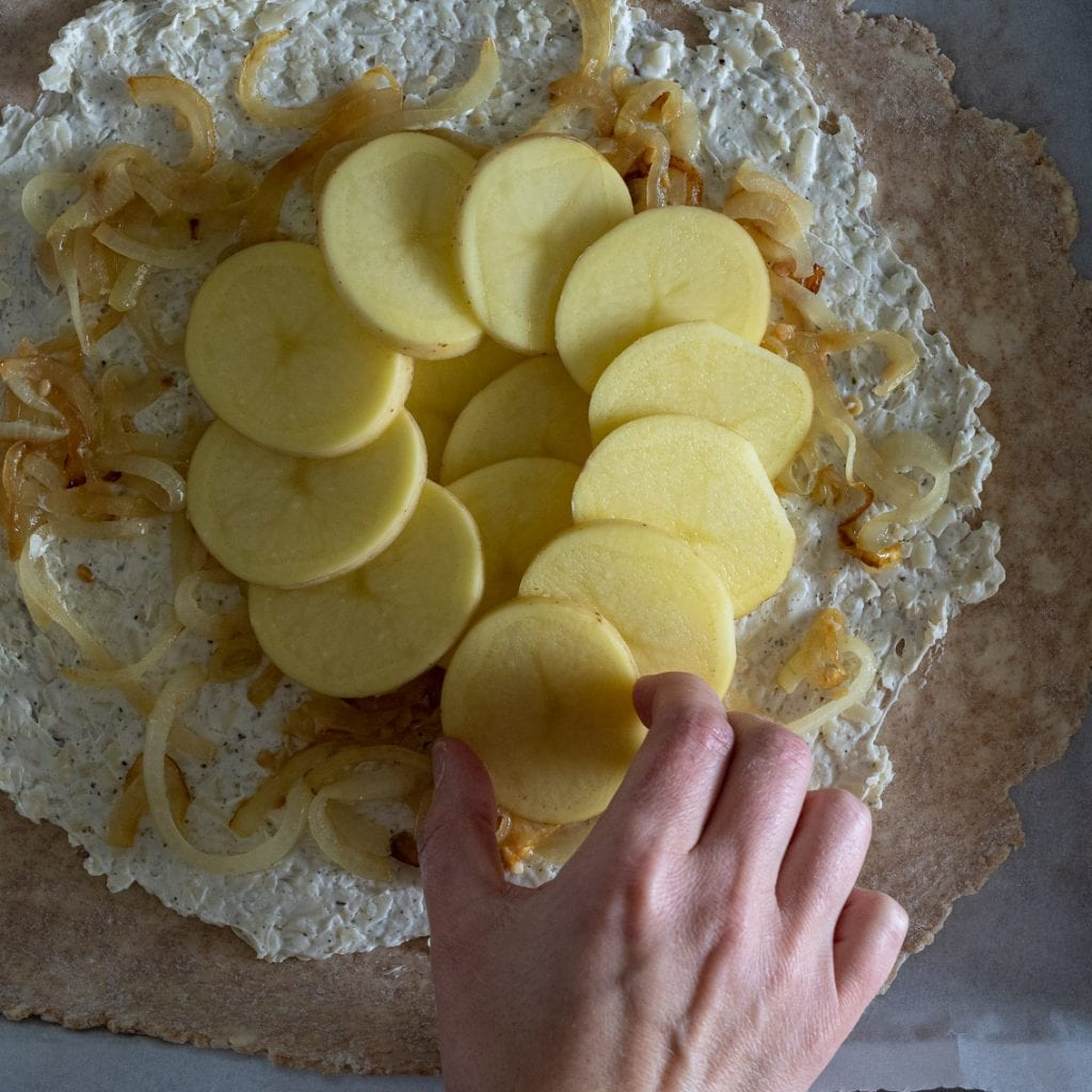woman layering yellow potatoes over gruyere filling for savory galette
