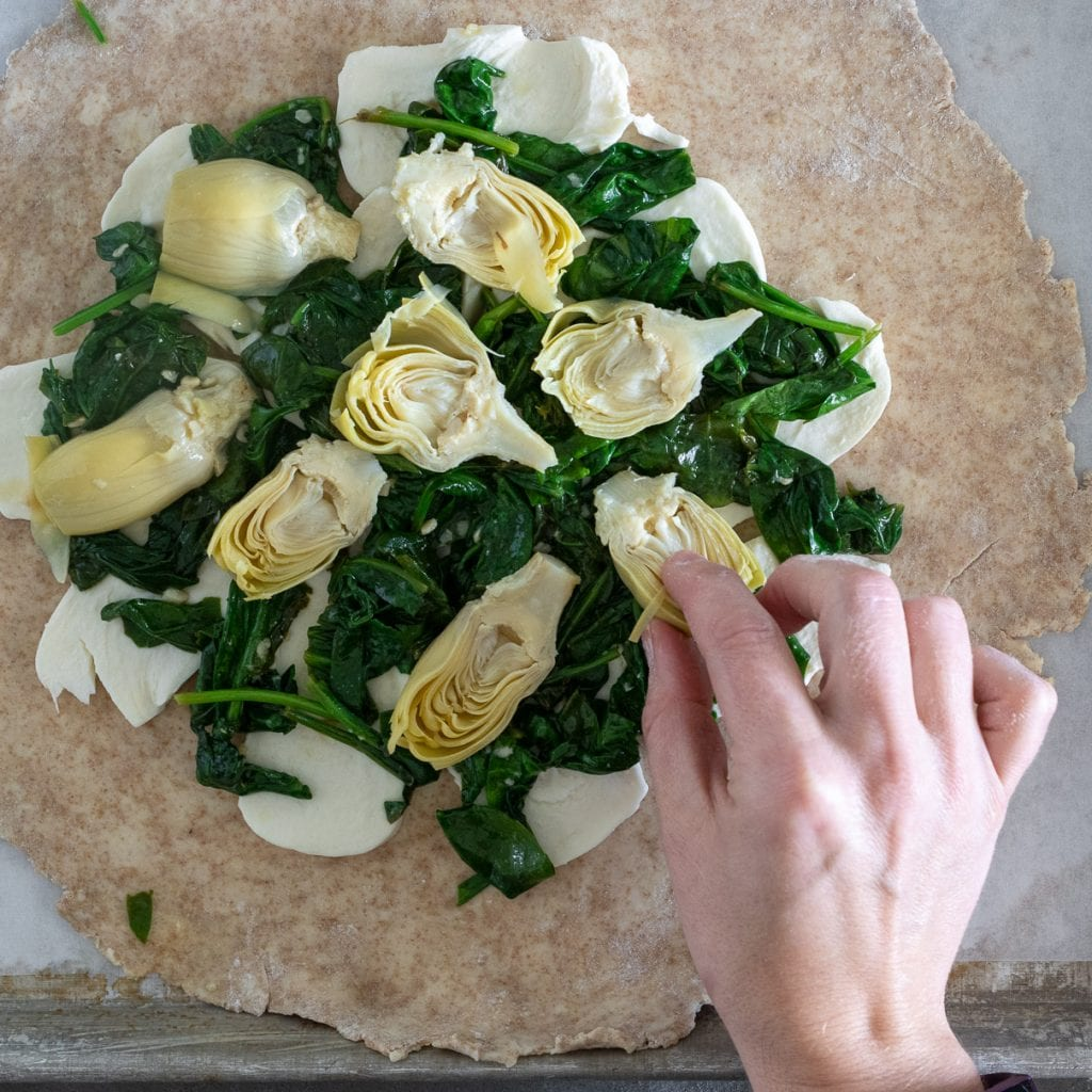 woman adding artichokes on top of sauteed spinach galette