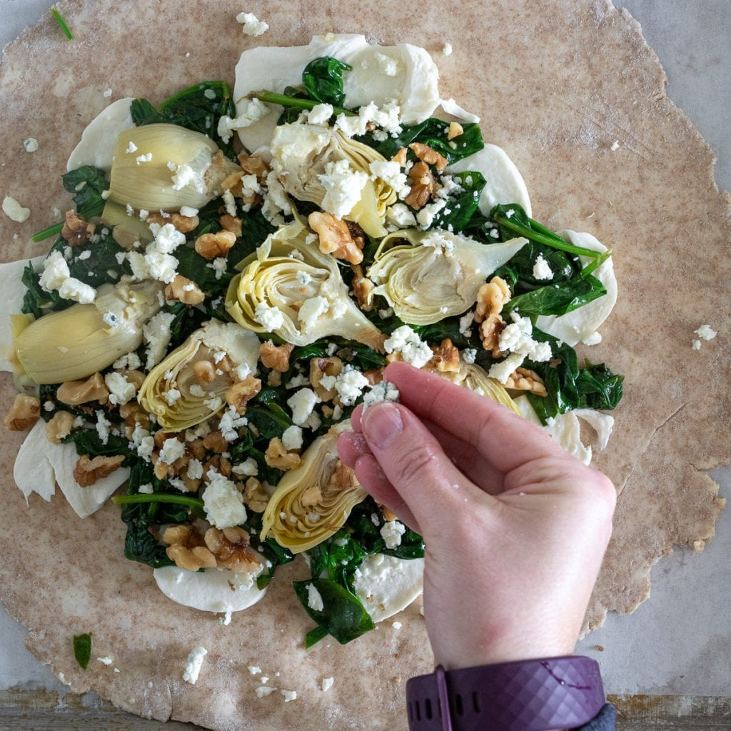woman adding bleu cheese sprinkles on top of savory galette with whole wheat crust