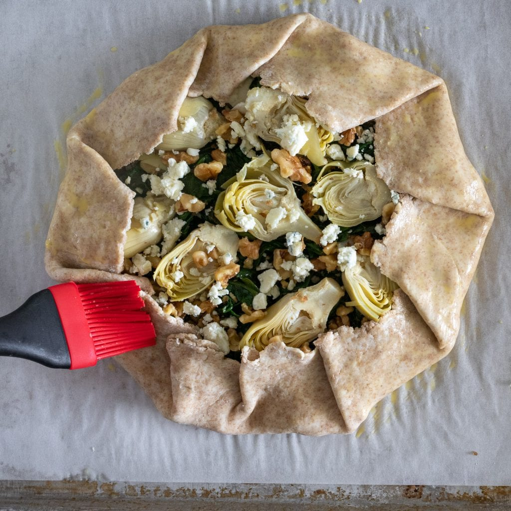 Simple Artichoke and Spinach Galette being brushed with egg wash