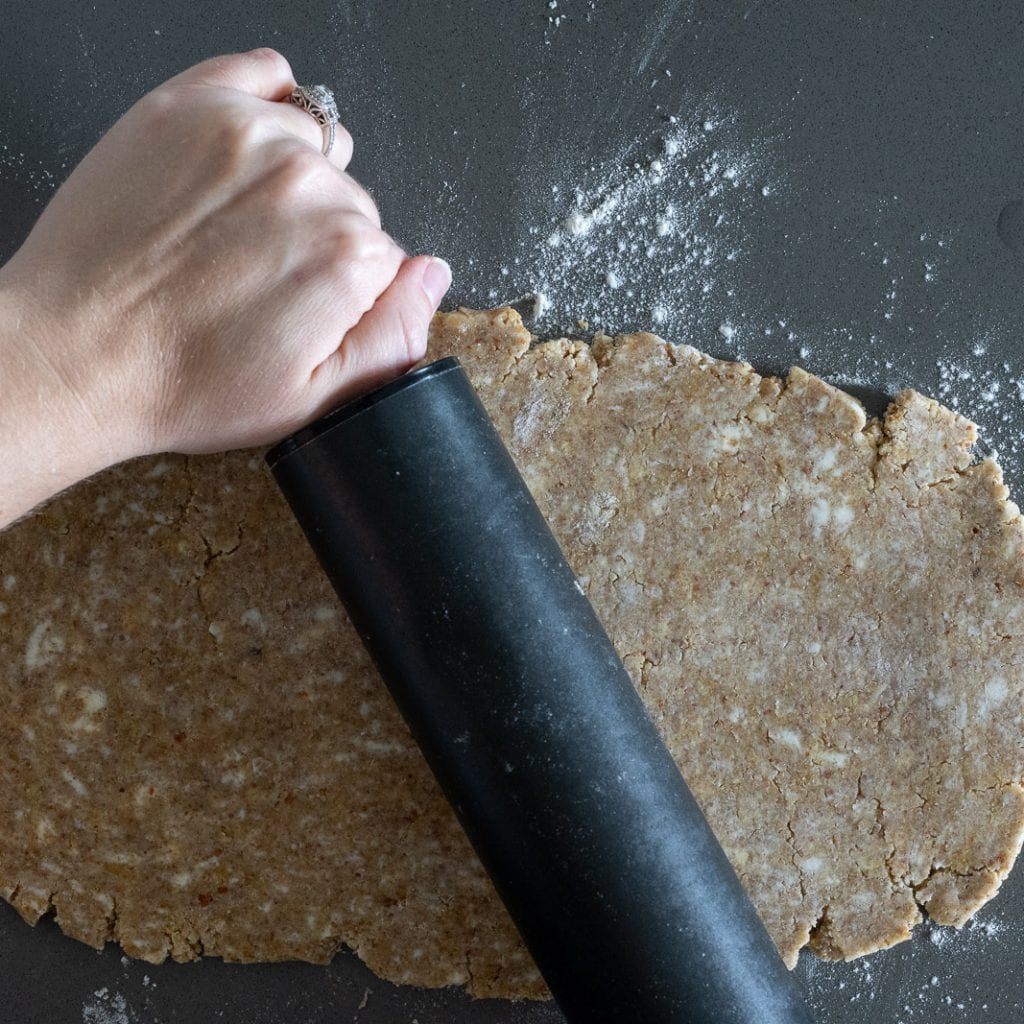 woman rolling almond short dough with a black rolling pin on counter for tart