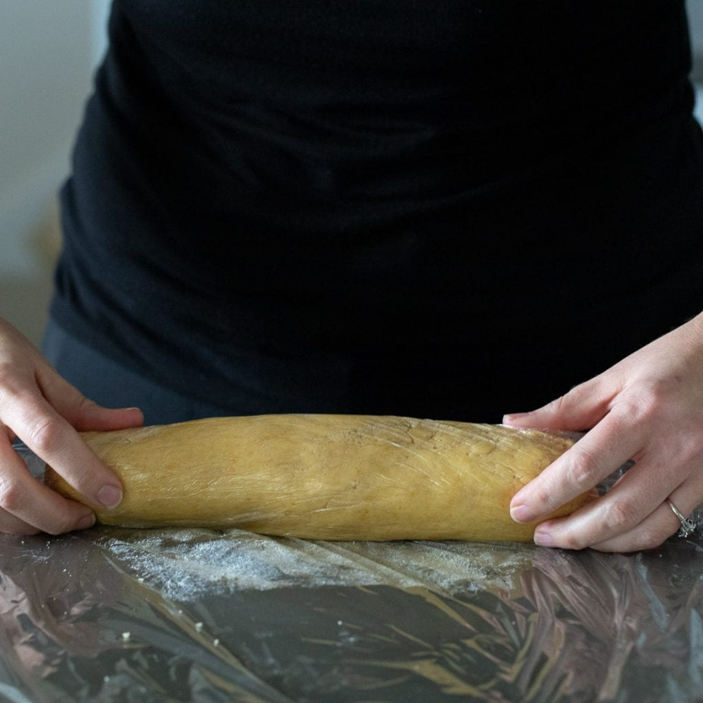 woman rolling cookie dough in saran wrap for chilling
