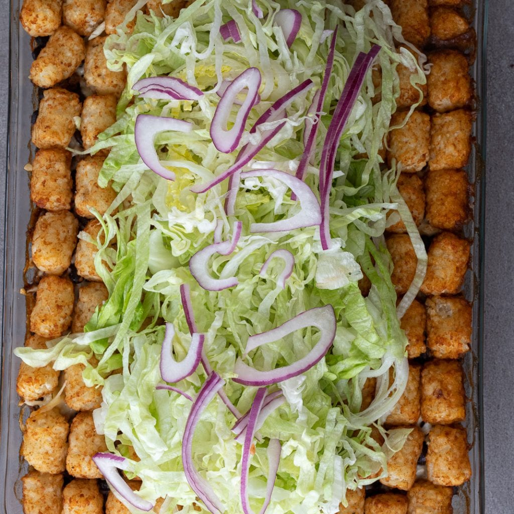 lettuce and red onions on tater tot casserole