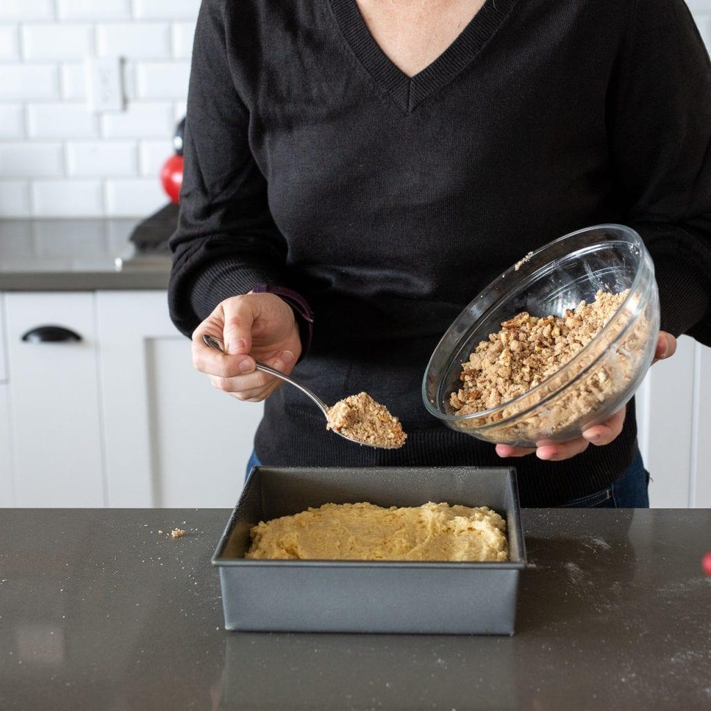 woman adding streusel to coffee cake in a 9x9 metal pan