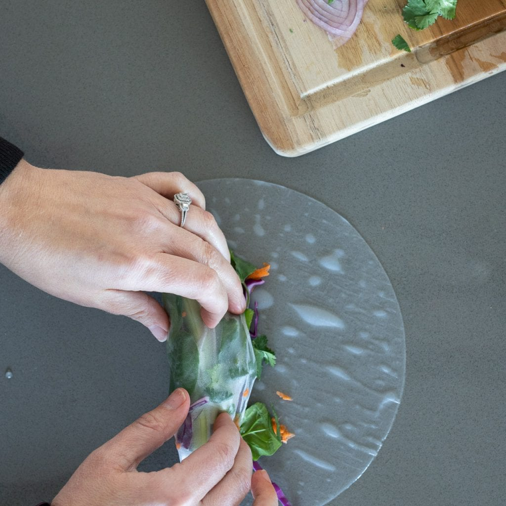 woman rolling vegetarian spring rolls