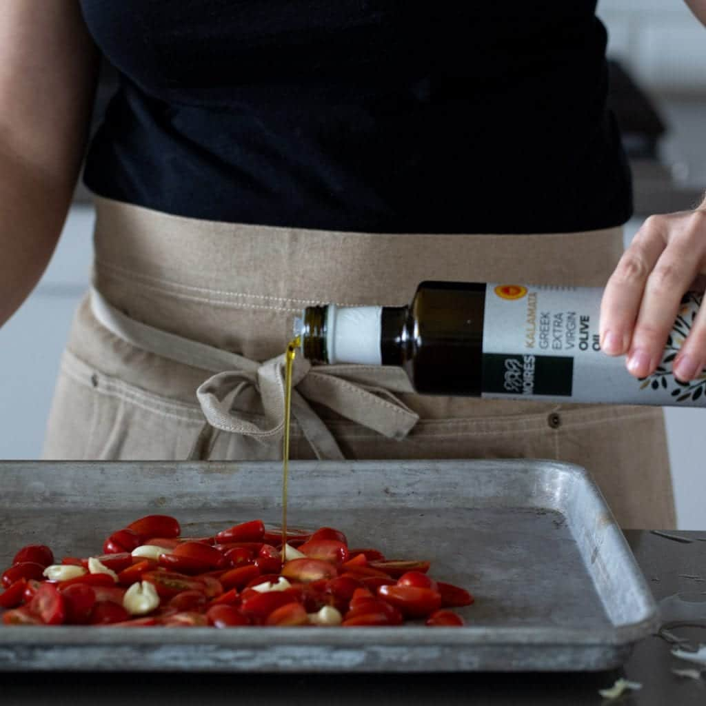 woman drizzling cherry tomatoes with olive oil