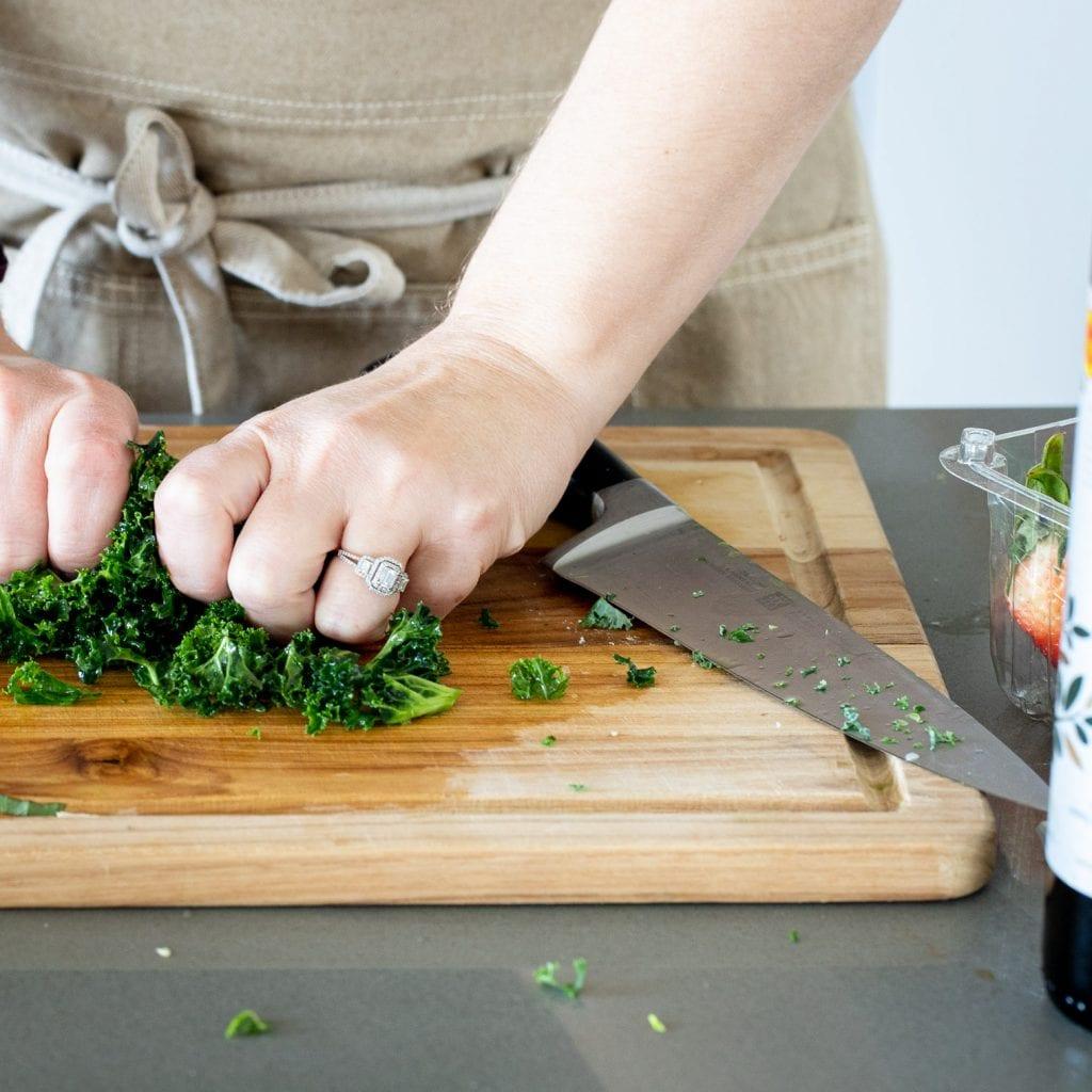 woman massaging kale on a wooden cutting board