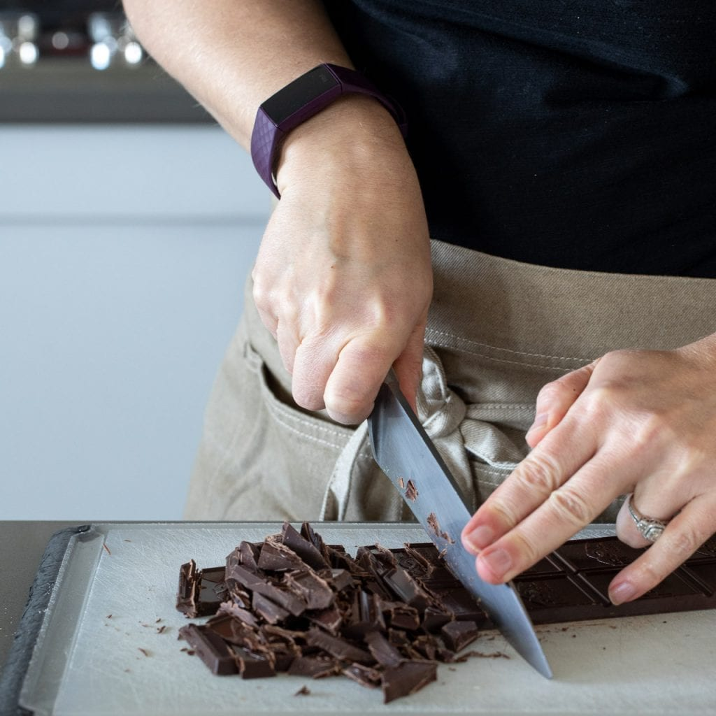 woman cutting dark chocolate on a white plastic cutting board with a chef's knife