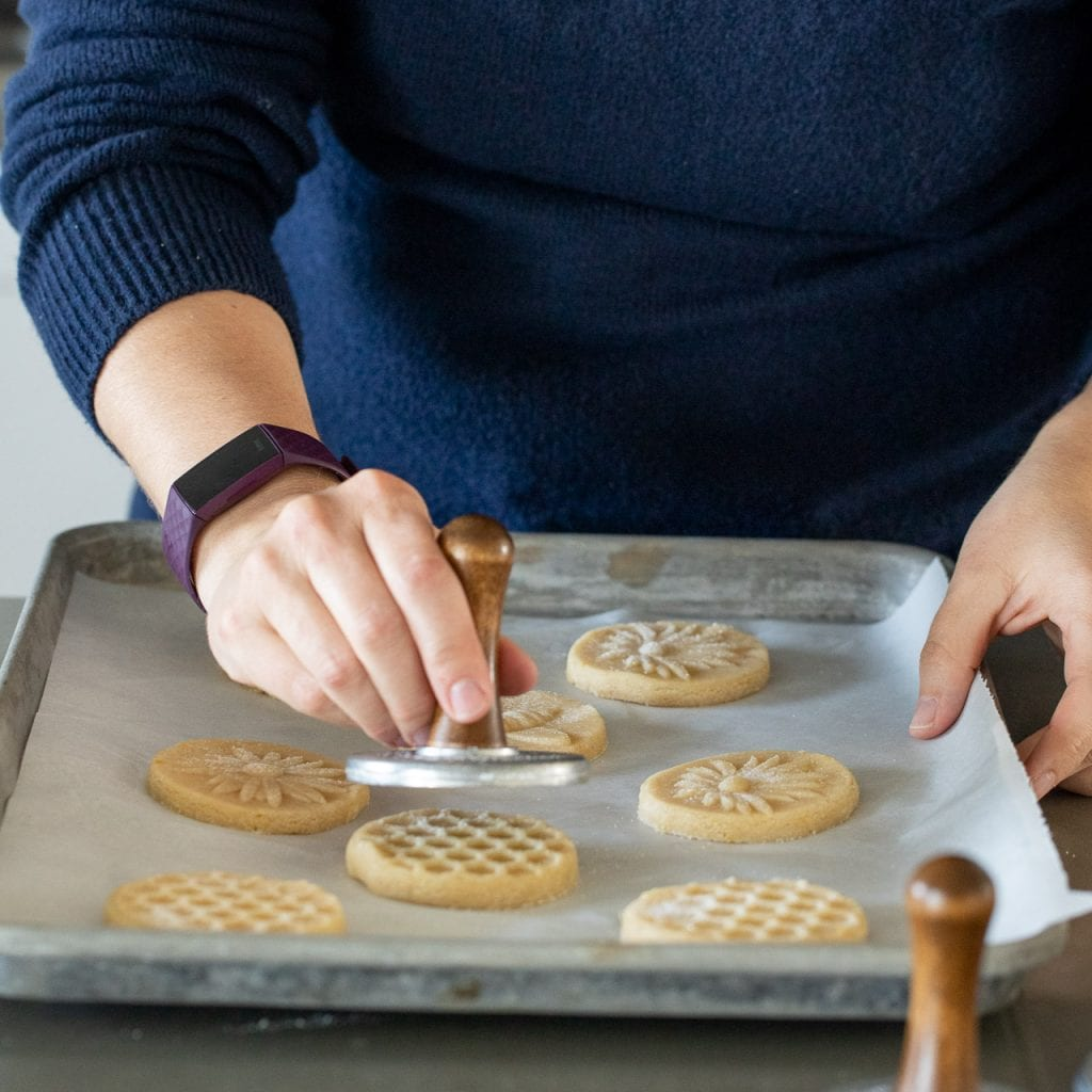 woman stamping cookies with a honeycomb cookie stamp