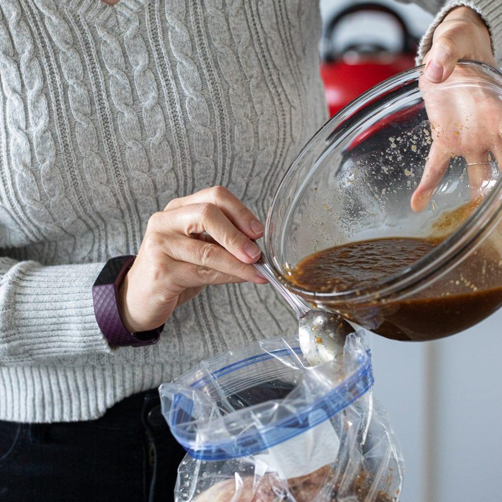 woman adding teriyaki marinade to chicken thighs in a ziplock bag