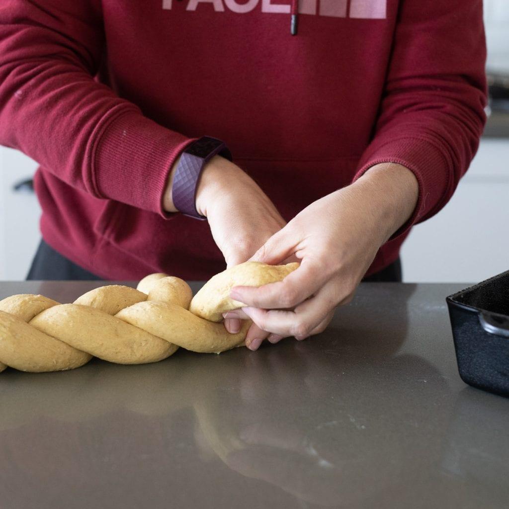 woman braiding oatmeal bread