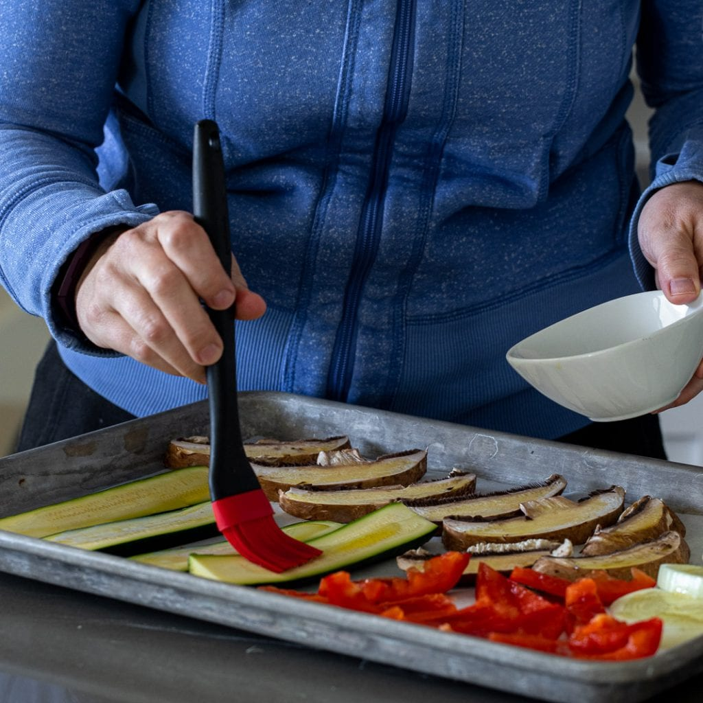 woman brushing olive oil on veggies for roasting with a red brush