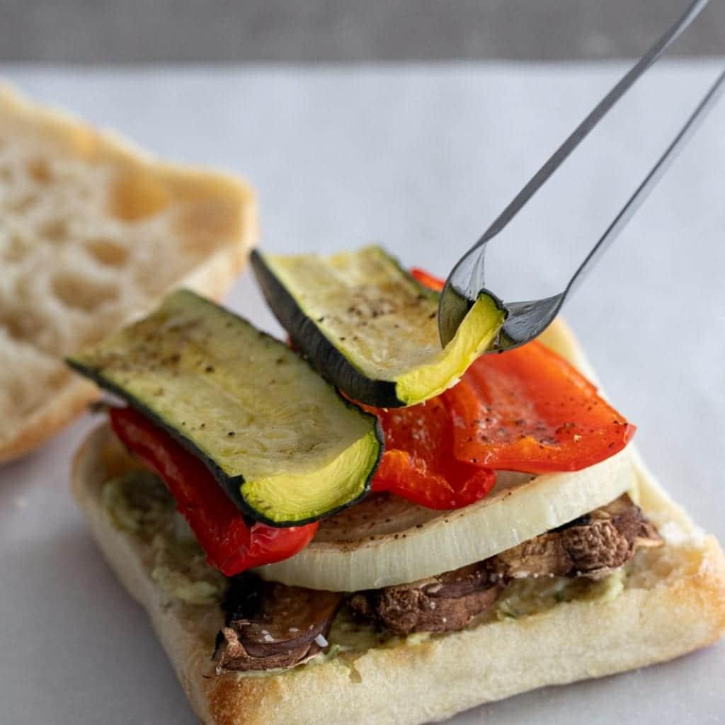 woman adding roasted zucchini to sandwich