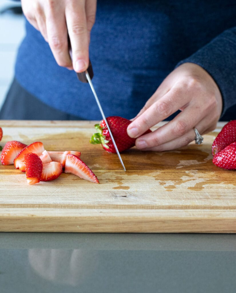woman cutting up strawberries on a wooden cutting board.
