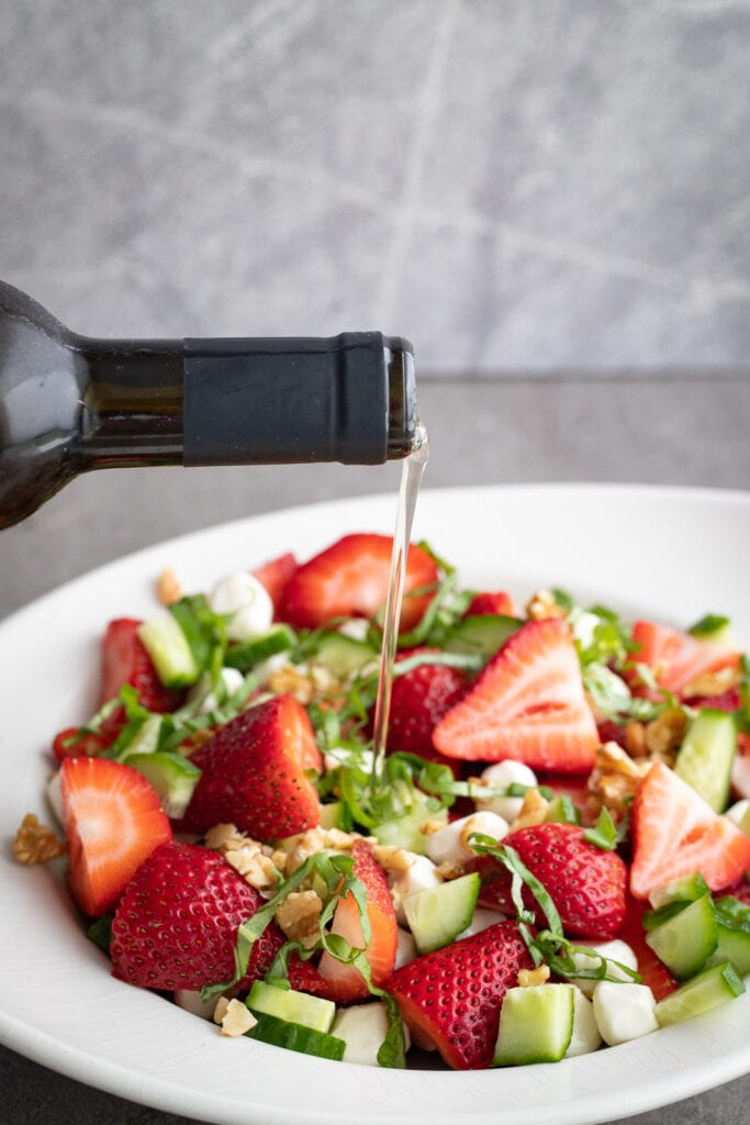 Simple Strawberry Basil Salad being poured with a white balsamic