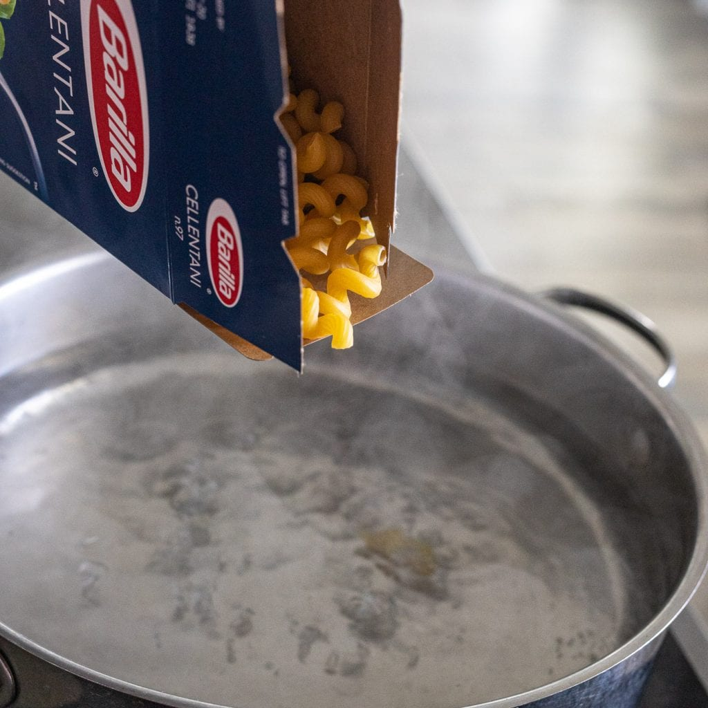 woman adding pasta to boiling pot of water.