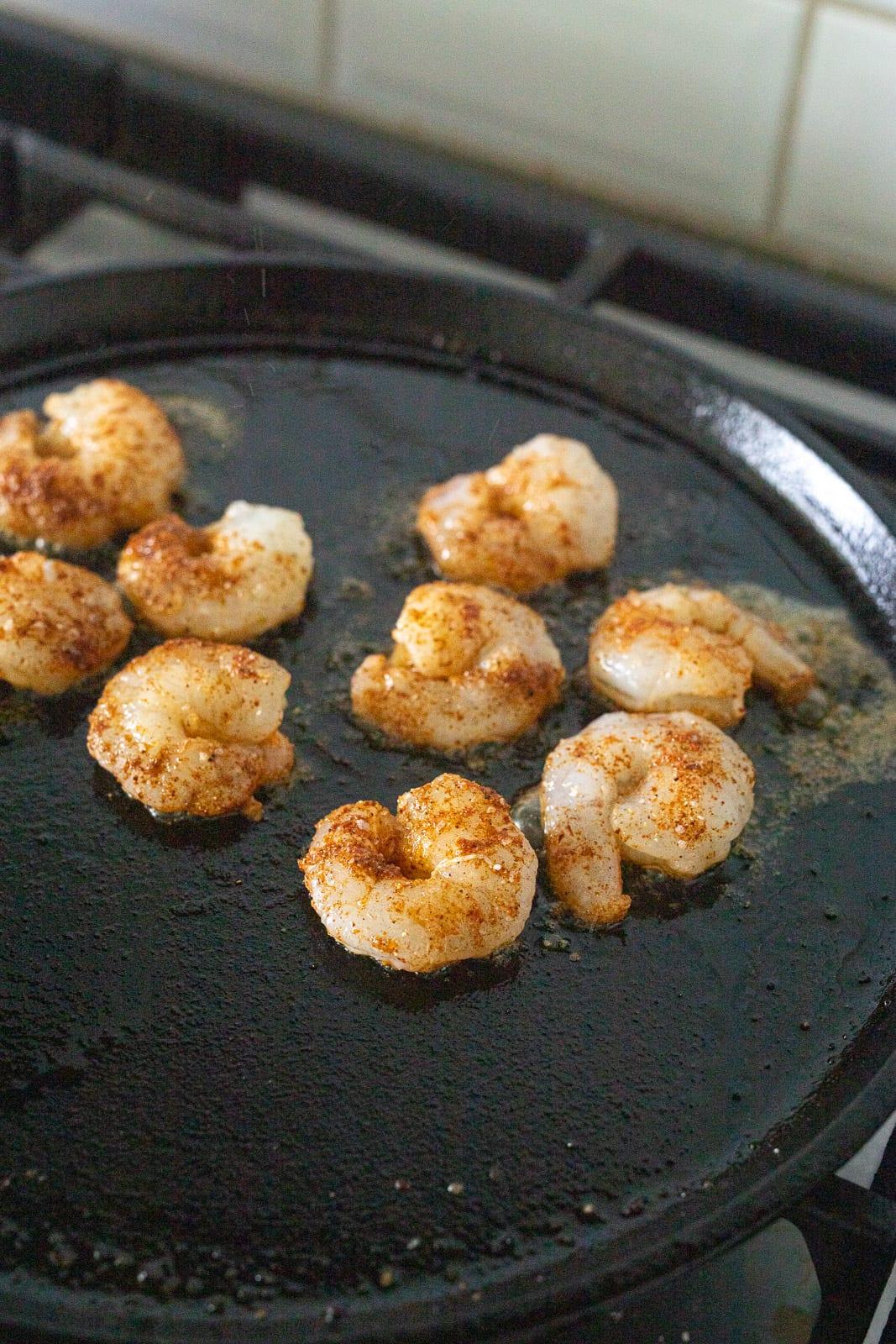 shrimp cooking on a cast iron griddle