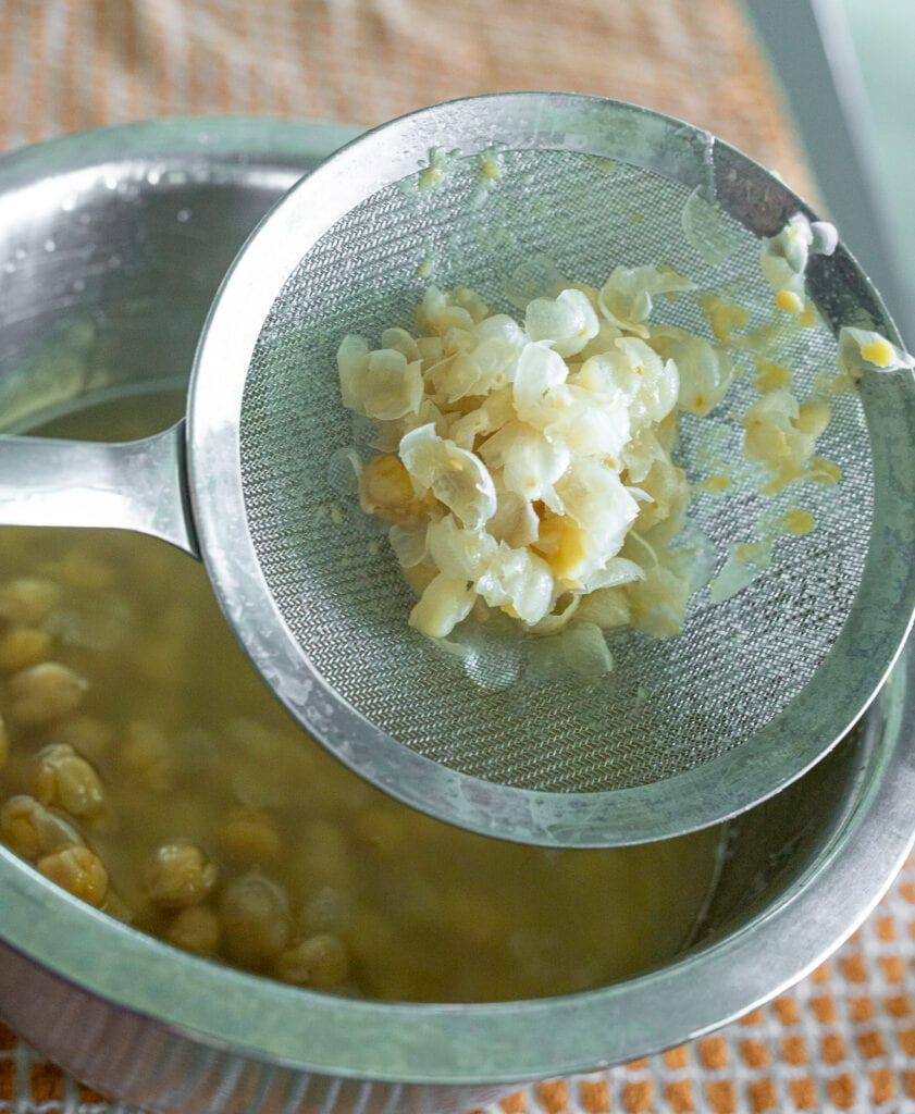 peeling the skins off chickpeas to make hummus