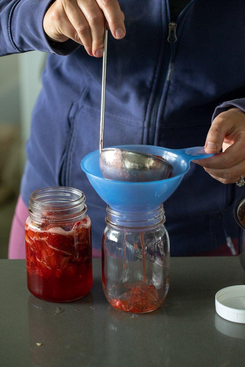 pouring hot jam through a funnel into a mason jar