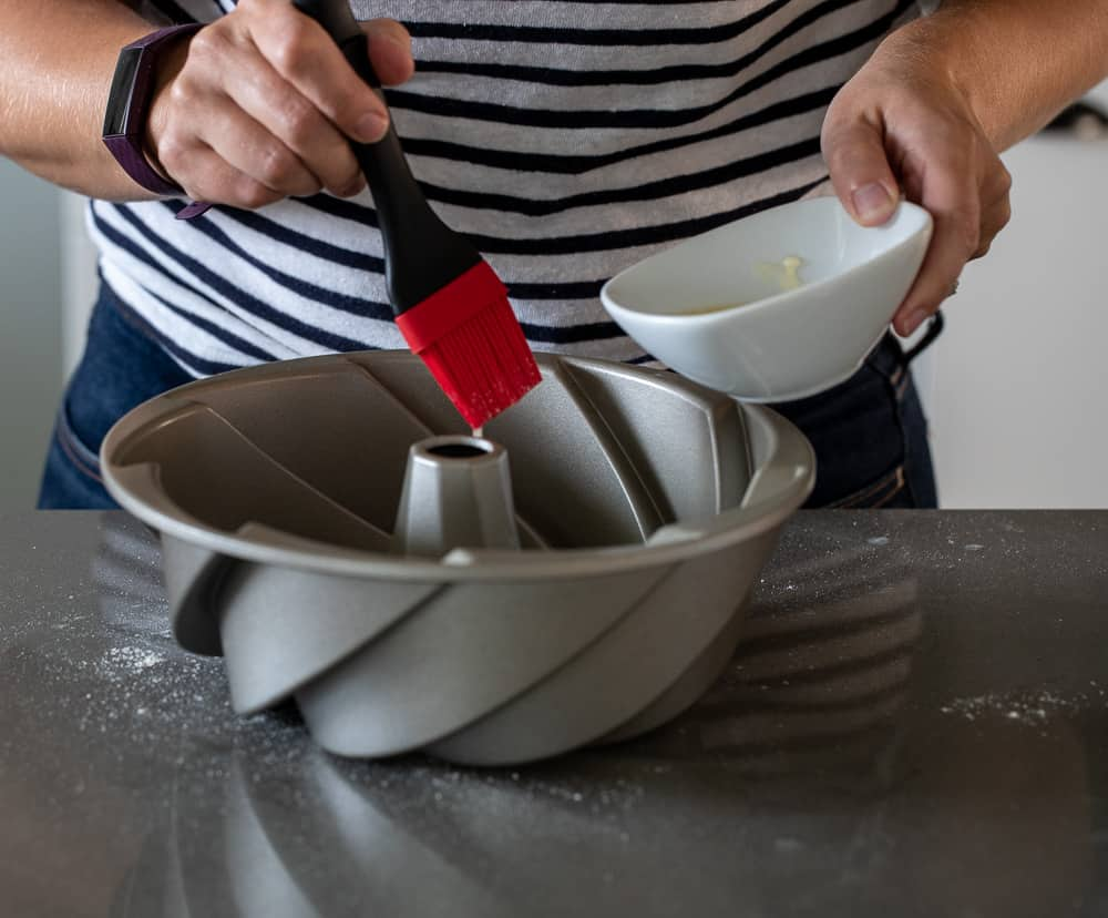 woman buttering bundt pan for chamomile cake