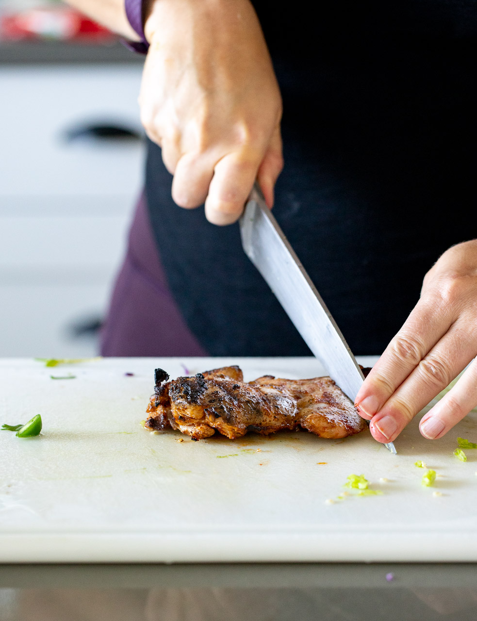 woman cutting grilled chicken thighs for tacos